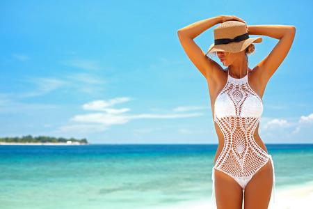 Mooie vrouw die gehaakte bikini poseren op het uitzicht op zee, strand levensstijl