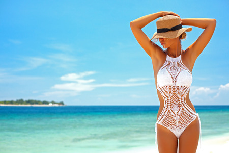 Piękna kobieta noszenie bikini szydełkowe stwarzających nad widokiem na morze, plaża styl życia