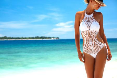 Bella donna che indossa bikini all'uncinetto propongono sopra la vista sul mare, stile di vita spiaggia