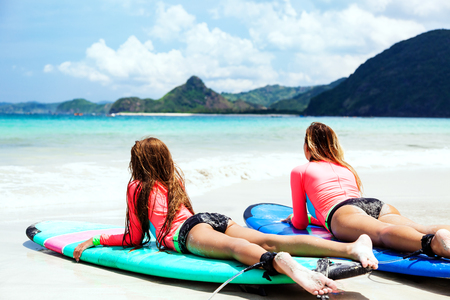 Mom with child are learning surfing together 版權商用圖片