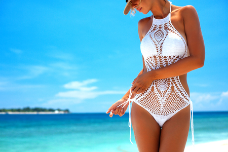 Beautiful woman wearing crochet bikini posing over the sea view, beach lifestyle