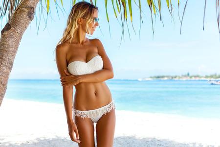 Jonge vrouw, gekleed in witte bikini poseren onder palm over uitzicht op zee bij tropisch strand