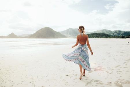 Vrouw draagt ??etnische vliegende jurk lopen op blote voeten op het strand, Lombok, Indonesië