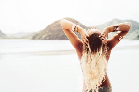 Mooie bohemian stijl en gelooid meisje op het strand in de zon