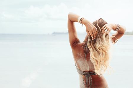 Hermoso estilo bohemio y chica curtida en la playa en la luz del sol Foto de archivo