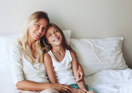 9 year old girl: Mom with her tween daughter relaxing in bed, positive feelings, good relations. Stock Photo