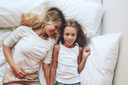 9 year old: Mom with her tween daughter relaxing in bed, positive feelings, good relations. Top view. Stock Photo