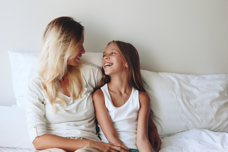 9 10 years: Mom with her tween daughter relaxing in bed, positive feelings, good relations. Stock Photo