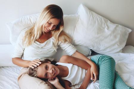pre teens: Mom with her tween daughter relaxing in bed, positive feelings, good relations. Stock Photo