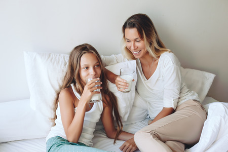 nine years old: Mom with her tween daughter relaxing in bed, positive feelings, good relations. Stock Photo