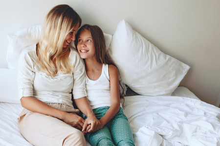 Mom with her tween daughter relaxing in bed, positive feelings, good relations. Banque d'images