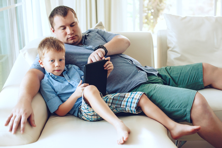 kids playing video games: Happy family resting on a sofa and using digital tablet together in living room Stock Photo