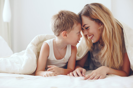 Jeune mère avec son 6 ans petit fils en pyjama sont relaxants et en jouant dans le lit le week-end ensemble, paresseux matin, scène chaleureuse et confortable.