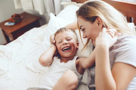 Jonge moeder met haar 6 jaar oude zoontje, gekleed in pyjama zijn ontspannen en spelen in het bed in het weekend samen, luie ochtend, warm en gezellig scene.