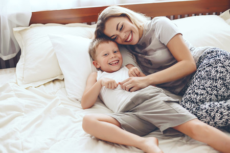 preschooler: Young mother with her 6 years old little son dressed in pajamas are relaxing and playing in the bed at the weekend together, lazy morning, warm and cozy scene.