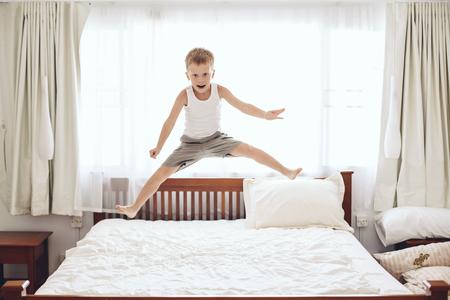 6 jaar oud jongetje springt op het bed van de ouders Stockfoto
