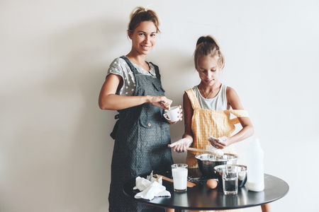 making fun: Mom with her 10 years old daughter dressed in linen aprons are cooking together over light wall, lifestyle photo series