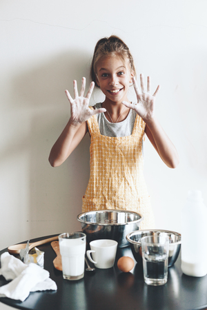 home cooking: 10 years old preteen girl dressed in cotton apron is cooking holiday pie on the table over wall, organic food, lifestyle photo