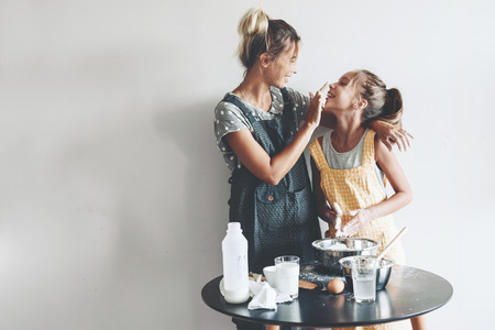 Mamma met haar 10 jaar oude dochter, gekleed in linnen schorten worden samen koken over lichte muur, lifestyle fotoserie