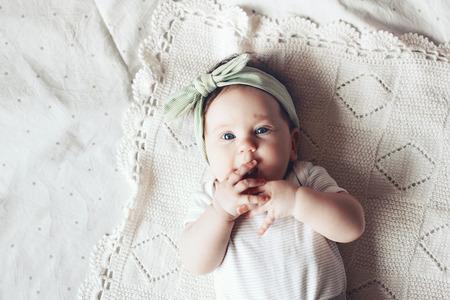 Retrato de una cinta de la flor del cordón 4 meses niña bonita vistiendo y se acuesta en una manta de ganchillo