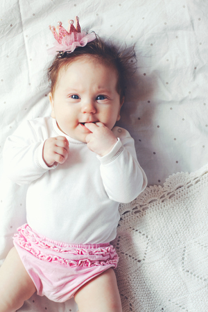 cintillos: Retrato de una niña linda 4 meses llevando la venda corona de la princesa y acostado en una cama con ropa de cama blanca del lunar, vista desde arriba