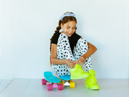 pre teen: Pre teen girl wearing cool fashion clothing and sneakers posing with colorful skateboard against white wall