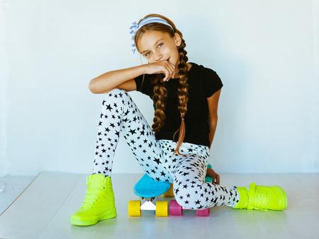 Pre tienermeisje dat koel mode kleding en sneakers poseren met kleurrijke skateboard tegen witte muur Stockfoto
