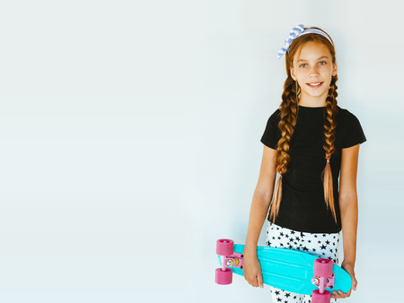 Pre teen girl wearing cool fashion clothing posing with colorful skateboard against white wall
