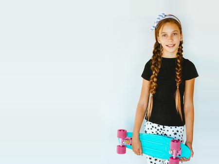 Menina pré adolescente, vestindo roupas de moda legal, posando com skate colorido contra parede branca Foto de archivo