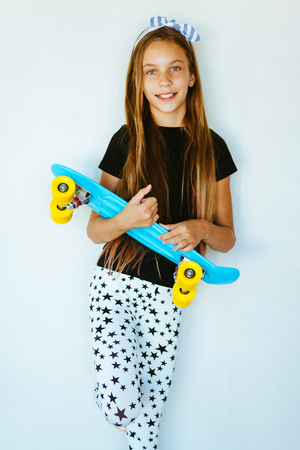 pre teen girl: Pre teen girl wearing cool fashion clothing posing with colorful skateboard against white wall