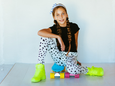 Pre teen girl wearing cool fashion clothing and sneakers posing with colorful skateboard against white wall