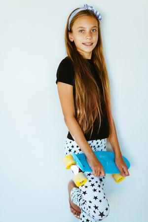 Pré fille adolescente porter des vêtements de mode cool posant avec planche à roulettes colorée contre le mur blanc
