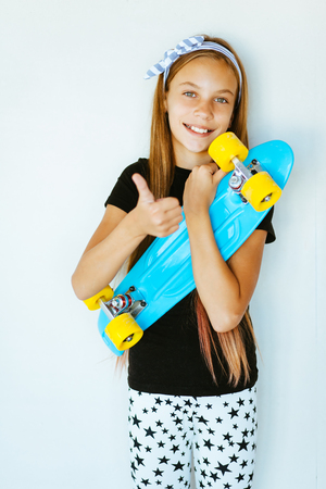 child model: Pre teen girl wearing cool fashion clothing posing with colorful skateboard against white wall