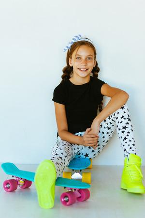 Vor jugendlich Mädchen tragen coole Mode Kleidung und Turnschuhe mit bunten Skateboard gegen die weiße Wand aufwirft Standard-Bild - 59763820