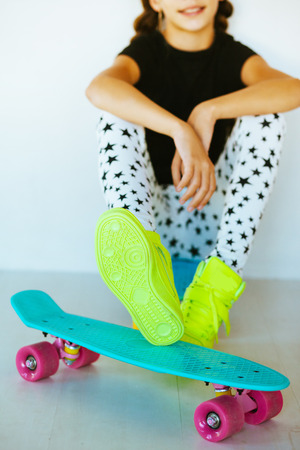 pre teen girl: Pre teen girl wearing cool fashion clothing and sneakers posing with colorful skateboard against white wall