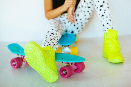 Pré fille adolescente porter des vêtements et des chaussures de sport de mode cool posant avec planche à roulettes colorée contre le mur blanc