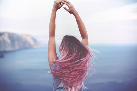 Женщина с розовым стоя волос на вершине горы над голубым видом на море, фото тонированное Фото со стока