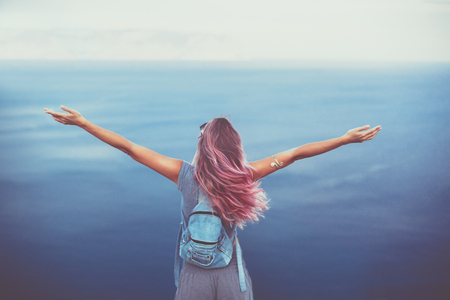 Woman with pink hair standing on the mountain top over blue sea view, photo toned Stock Photo