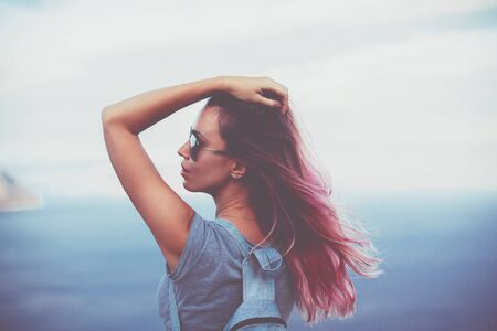 colored: Woman with pink hair standing on the mountain top over blue sea view, photo toned Stock Photo