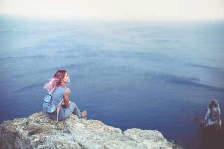 top mountain: Woman with pink hair standing on the mountain top over blue sea view, photo toned Stock Photo
