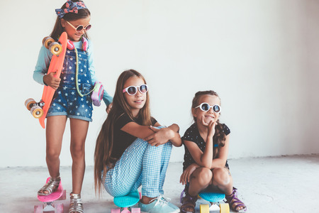 Company of children of different ages wearing cool fashion clothing posing with colorful skateboards against white wall, urban style Stock Photo