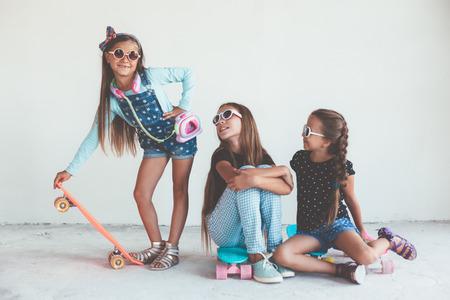 chicas adolescentes: Compañía de niños de diferentes edades que llevan la ropa fresca de la manera que presenta con monopatines de colores contra la pared blanca, estilo urbano