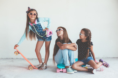 preteens girl: Company of children of different ages wearing cool fashion clothing posing with colorful skateboards against white wall, urban style Stock Photo