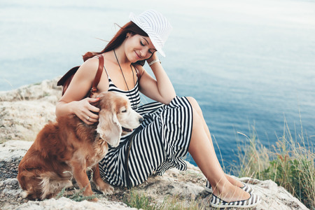 Woman hugs with her dog sitting on mountain over sea view.