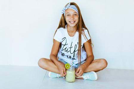 흰색 벽에 아름 다운 십 대 소녀 마시는 스무디 쉐이크 스톡 콘텐츠