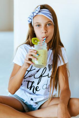 tween: Beautiful teenage girl drinking smoothie shake against white wall