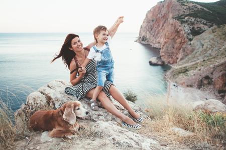 mama e hijo: Madre recorre con su hijo y perro en la montaña sobre la vista al mar, fin de semana familiar. Foto de archivo