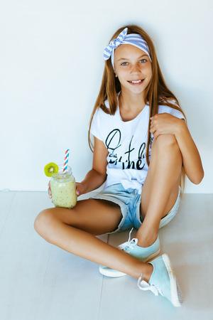 Mooie tiener het drinken smoothie schudden tegen witte muur