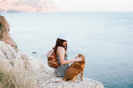 Mujer abraza con su perro sentado en la montaña sobre la vista al mar.