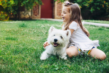 아이 영어 뒷마당에서 잔디에 하이랜드 화이트 테리어 강아지와 함께 연주